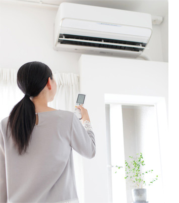 asian lady controlling air conditioner keeping cool air inside insulated walls